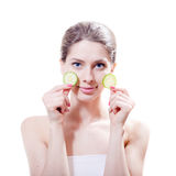 In spa: young beautiful woman attractive girl standing with slices of cucumber in the hands & looking at camera on white Stock Photo