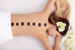 Spa. Young woman doing hot stone therapy. Professional beautician massaging female back by stones. Spa. Young woman doing hot stone therapy stock photo