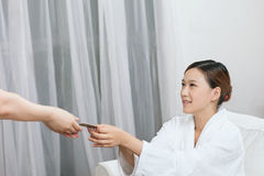 A spa young woman handing out a bank card. A spa young women handing out a bank card at spa salon, indoors Stock Image