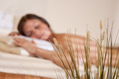 Spa - Young woman at wellness massage treatment. Spa - Young woman at wellness therapy treatment relaxing, focus on grass on foreground stock photos