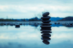 Spa zen stones. Over blue cloudy sky background and water reflection Stock Photography