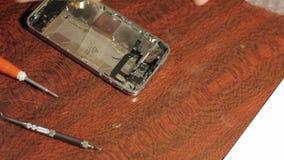 Spaanders en details van smartphone De meester demonteerde mobiel apparaat voor detail stock videobeelden