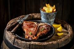 Spaanders en riblapje vlees op oud vat Stock Fotografie