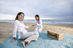 Spaans moeder en kind die picknick op strand hebben stock foto's