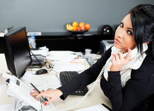 Spaans wijfje op telefoon in bureau Stock Afbeeldingen