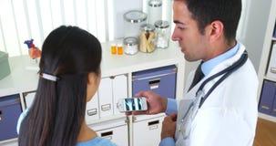 Spaanse arts die smartphone gebruiken om röntgenstraal aan patiënt te tonen Stock Afbeeldingen