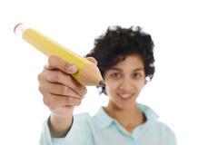 Spaanse bedrijfsvrouw die reusachtig geel potlood houden Stock Afbeelding