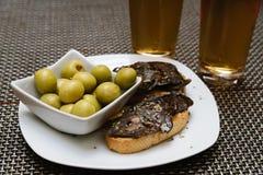 Spaanse die tapa met olijven en chorizo wordt geplaatst stock foto
