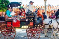 Spaanse families in traditionele kleding die in een paard getrokken vervoer reist in April Fair, de Markt van Sevilla stock foto's