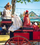 Spaanse families in traditionele kleding die in een paard getrokken vervoer reizen in April Fair, Sevilla Eerlijke Feria de Sevil stock foto
