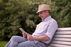 Spaanse hogere mens in de lezingstablet van de de zomerhoed in de ruimte van het parkexemplaar royalty-vrije stock afbeelding