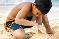 Spaanse jongen die een zandkasteel bouwt Royalty-vrije Stock Foto's