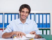 Spaanse kerel bij bureau sorterende brieven Royalty-vrije Stock Fotografie