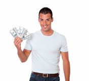 Spaanse kerel die en dollars glimlachen houden Royalty-vrije Stock Afbeelding