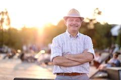 Spaanse mens in de zomerhoed met het gevouwen handen glimlachen die camera bekijken die zich op stadspark bevinden royalty-vrije stock foto's