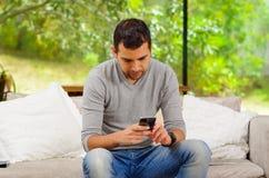 Spaanse mens die denimjeans met grijze sweater dragen Stock Fotografie