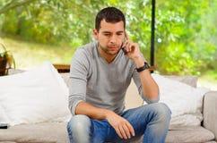 Spaanse mens die denimjeans met grijze sweater dragen Stock Foto's