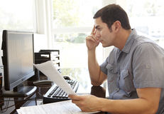 Spaanse Mens die in Huisbureau werken Stock Foto