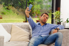 Spaanse mens die jeans en blauwe overhemdszitting dragen Royalty-vrije Stock Foto