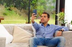 Spaanse mens die jeans en blauwe overhemdszitting dragen Stock Fotografie