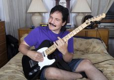 Spaanse mens die in slaapkamer met gitaar rusten Royalty-vrije Stock Foto