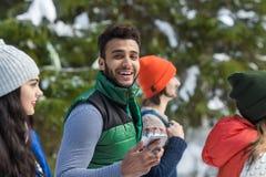Spaanse Mens die Slimme Telefoon met behulp van die Online Sneeuw Forest Young People Group Walking babbelen de Openluchtwinter Stock Foto's