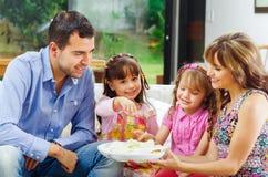 Spaanse ouders met twee dochters die van a eten Stock Foto's