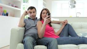 Spaanse Paarzitting op Sofa Watching-TV samen stock videobeelden