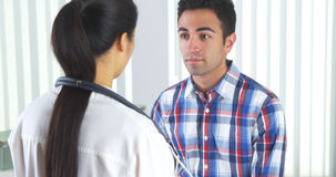 Spaanse patiënt die arts bekijken stock fotografie