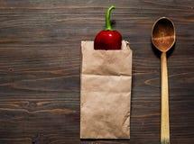 Spaanse peper in een document zak en een houten lepel op een donkere houten oppervlakte, ruimte voor tekst, hoogste mening Stock Afbeeldingen