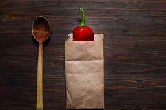 Spaanse peper in een document zak en een houten lepel op een donkere houten oppervlakte, ruimte voor tekst, hoogste mening Royalty-vrije Stock Afbeelding