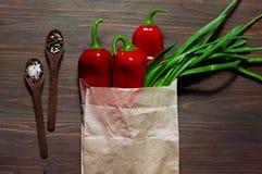 Spaanse peper, groene ui in een document zak en houten lepel met kruid op een donkere houten oppervlakte, ruimte voor tekst, hoog Stock Foto's