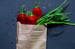Spaanse peper, groene ui in een document zak op een blauwe oppervlakte, ruimte voor tekst, hoogste mening, concept een gezonde vo Stock Foto's