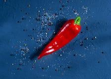 Spaanse peper op een donkerblauwe oppervlakte tegen een achtergrond van kruiden, ruimte voor tekst, hoogste mening Royalty-vrije Stock Foto