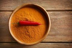 Spaanse peperpoeder en ruwe peper in kom Stock Foto