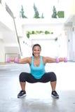 Spaanse sportvrouw die hurkzit met roze domoor twee doen, openlucht Stock Fotografie