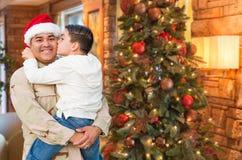 Spaanse Strijdkrachtenmilitair Wearing Santa Hat Hugging Son royalty-vrije stock afbeeldingen