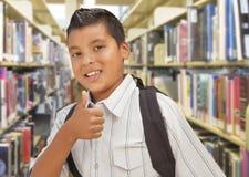 Spaanse Student Boy met Duimen omhoog in de Bibliotheek Stock Fotografie