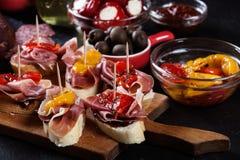 Spaanse tapas met plakken jamon serrano en geroosterde peper Ook legden de olijven, salami, uien in, en de peper vulde met kaas Stock Fotografie