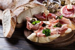 Spaanse tapas met plakken jamon serrano, salami, olijven en kaaskubussen op een houten lijst Stock Afbeelding