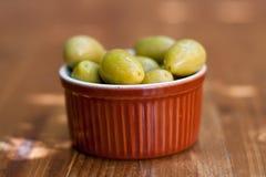 Spaanse tapas organische groene olijven van het keukenvoedsel in een bruine kleischotel Houten lijstachtergrond, zachte selectiev Royalty-vrije Stock Afbeelding
