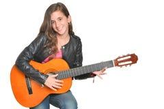 In Spaanse tiener die een akoestische gitaar spelen stock foto