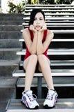 Spaanse Tienervrouw Sittig op Metaalbleachers Chin In Hands stock fotografie