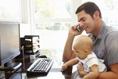 Spaanse vader met baby het werken in huisbureau Stock Foto's