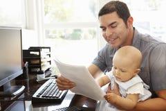 Spaanse vader met baby het werken in huisbureau Royalty-vrije Stock Foto