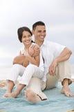 Spaanse vader met meisje op stranddeken Stock Afbeelding