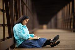 Spaanse van de Vrouwenzitting en Lezing Bijbel op een Brug stock afbeelding
