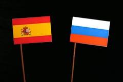Spaanse vlag met Russische vlag op zwarte stock foto's