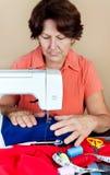 Spaanse vrouw die aan een naaimachine werkt Stock Foto's