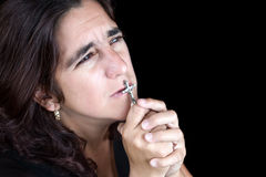 Spaanse vrouw die en een kruisbeeld bidden kussen Royalty-vrije Stock Fotografie